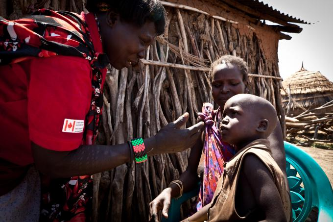 A Save the Children community health worker, Cecilia, performs a follow up check on 2-year-old Loge who had been suffering from pneumonia. (Colin Crowley/Save the Children)