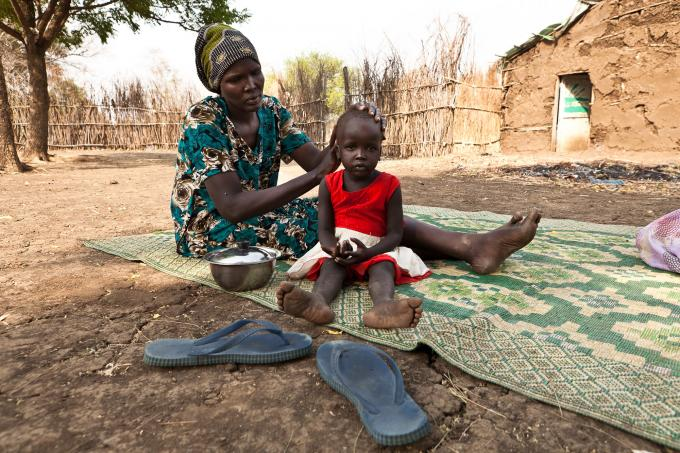 Martha, a member of a community farming group supported by Save the Children, outside her home in Pagak, Upper Nile state with her youngest child, 18-month-old Nyamalakal. (Colin Crowley/Save the Children)