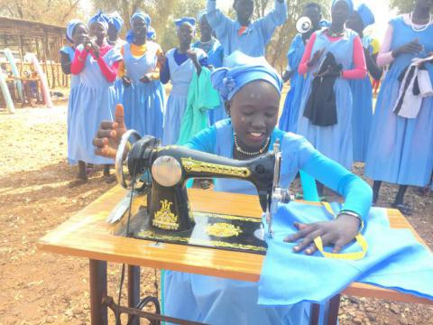 Achan* 16, demonstrates how to make clothes using her new sewing machine given by Save the Children.